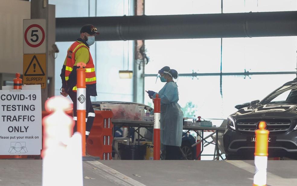 Funcionários trabalham em estação de testes de Covid-19 em Melbourne, na Austrália, na quinta-feira (4) — Foto: AP Photo/Hamish Blair